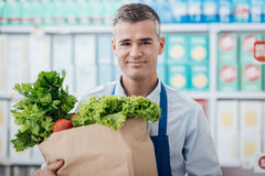 Shop assistant holding a grocery bag Stock Image