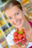 Shop assistant holding punnet strawberries Royalty Free Stock Images