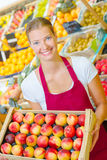 Shop assistant holding tray nectarines. Shop assistant holding tray of nectarines Royalty Free Stock Photo