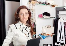 Shop assistant with laptop working in store Royalty Free Stock Images