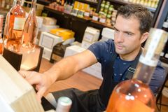 Shop assistant in liquor store royalty free stock photos
