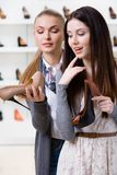 Shop assistant offers footwear for the customer Stock Photography