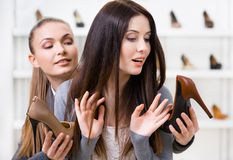 Shop assistant offers heeled shoes for the customer Royalty Free Stock Photography