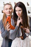 Shop assistant offers shoes for the customer. Shop assistant offers shoes for the female customer in the shopping center Royalty Free Stock Image