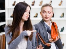 Shop assistant offers stylish shoes for the customer Royalty Free Stock Photography
