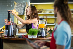 Shop assistant preparing juice at health grocery shop Stock Photography