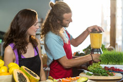 Shop assistant preparing juice at health grocery shop Stock Photo
