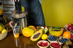 Shop assistant preparing papaya juice Stock Images