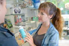 Shop assistant recommending spray to customer stock image