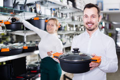 Shop assistant recommends the casseroles Stock Images