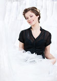 Shop assistant selects a proper dress. For the client, on white background Royalty Free Stock Photos