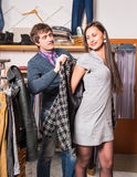Shop assistant showing coat to beautiful woman Stock Photo