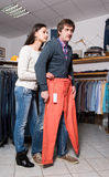 Shop assistant showing jeans to man Royalty Free Stock Images