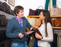 Shop assistant showing  leather bag to beautiful woman Royalty Free Stock Photo