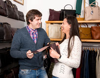 Shop assistant showing leather bag to beautiful woman Stock Photos
