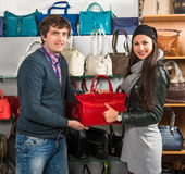 Shop assistant showing red leather bag to beautiful girl Royalty Free Stock Photography