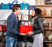 Shop assistant showing red white leather bag to beautiful girl Stock Images