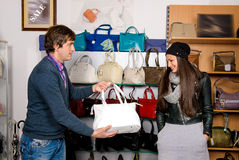 Shop assistant showing white bag to beautiful girl Stock Photos