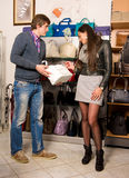 Shop assistant showing white bag to beautiful girl Royalty Free Stock Photo