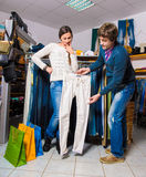 Shop assistant showing white jeans to beautiful gir Stock Image