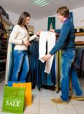 Shop assistant showing white jeans to beautiful gir Royalty Free Stock Photo