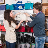 Shop assistant showing white leather bag to beautiful girl. In the mall Royalty Free Stock Photos