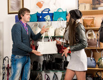 Shop assistant showing white leather bag to beautiful girl Stock Photo