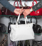 Shop assistant showing white leather bag to woman Royalty Free Stock Photo