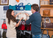 Shop assistant showing white leather bag to woman Stock Photography