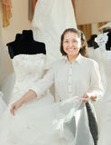 Shop assistant shows bridal dress Royalty Free Stock Photo