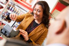 Shop assistant smiling while swiping credit card. In supermarket with customer in the foreground Royalty Free Stock Image