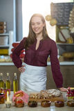 Shop assistant standing at the counter with oil bottle, pickle and bread. In grocery shop Royalty Free Stock Photography