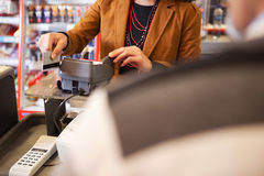 Shop assistant swiping credit card. In supermarket with customer in the foreground Royalty Free Stock Image