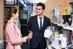 Shop assistant working with customer. Happy shop assistant working with customer at small household appliances section Stock Photo