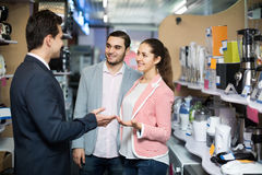 Shop assistant working with customer. Happy spanish shop assistant working with customer at small household appliances section Royalty Free Stock Image
