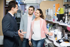 Shop assistant working with customer. Shop assistant working with positive american  customer at small household appliances section Royalty Free Stock Photos