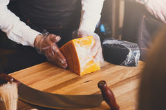 Shop assistant wrapping a piece of cheese at counter Stock Photography