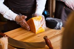 Shop assistant wrapping a piece of cheese at counter Royalty Free Stock Photo