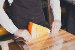 Shop assistant wrapping a piece of cheese Royalty Free Stock Images