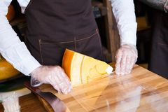 Shop assistant wrapping a piece of cheese Stock Photography