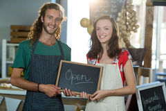 Shop assistants holding open sign board. At grocery shop royalty free stock images