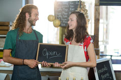 Shop assistants holding open sign board. At grocery shop stock photography