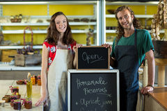 shop assistants holding open sign board stock image