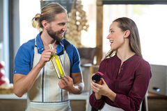 Shop assistants interacting while holding olive oil and pickle bottles royalty free stock photo