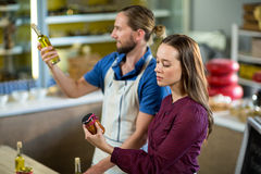 Shop assistants looking at olive oil and pickle bottles stock image