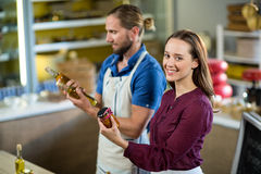 Shop assistants looking at olive oil and pickle bottles. At grocery shop royalty free stock photos