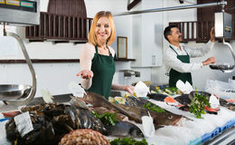 Shop assistants selling fresh fish. And chilled seafood stock photography