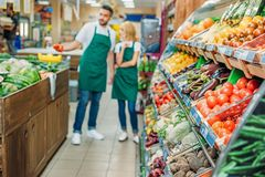 Shop assistants working together. In grocery shop stock photography