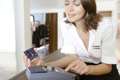 Shop Attendant Sweeping Credit Card at Store Counter Stock Image