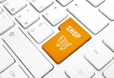 Shop business concept. Orange shopping cart button or key on white keyboard Stock Images